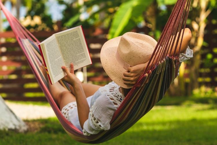 Happy beautiful woman in white dress relaxing in hammock.